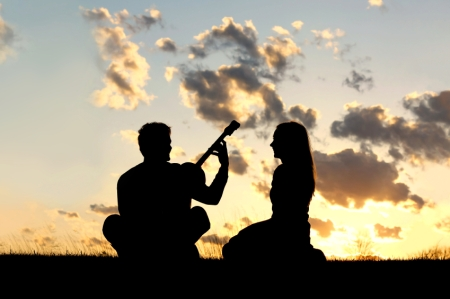 Silhouette of Couple Playing Guitar at Sunset