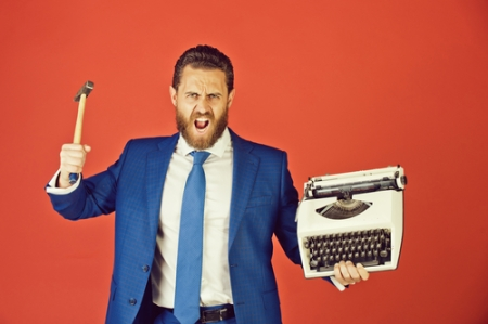 business man, aggressive businessman with typewriter and hammer