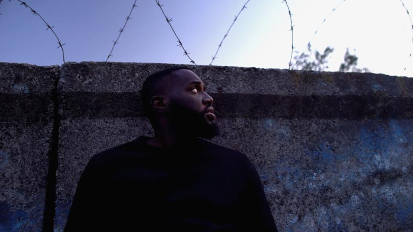 Imprisoned afro-american man looking at barbed wire, refugee camp, hopelessness